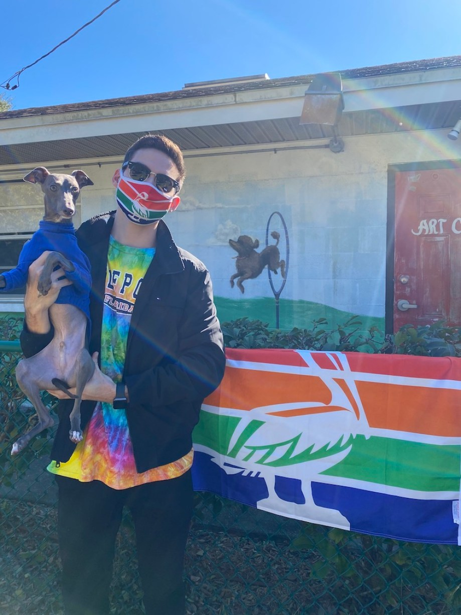 A man in a face mask holds an Italian greyhound in a sweater outside