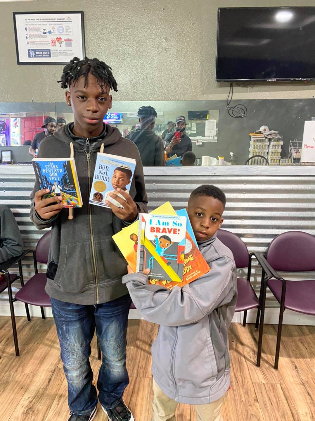 Two young boys holding books up to the camera