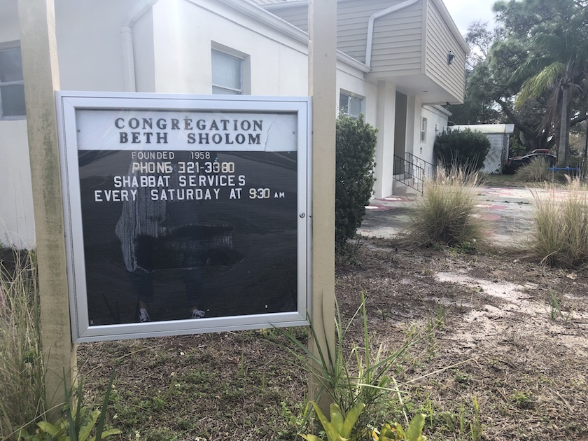 "A synagogue sign that reads ""Congregation Beth Shalom"" with worship times."