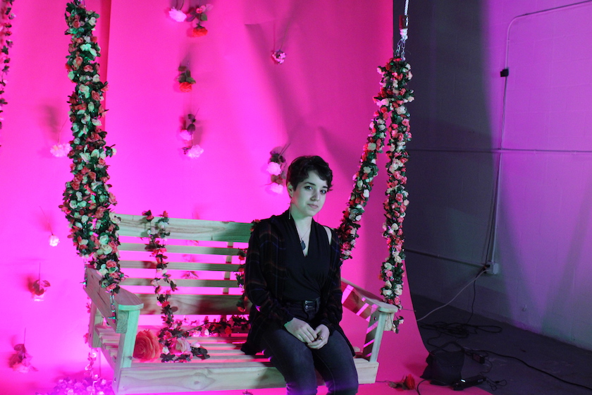 A woman sitting on a swing in an art exhibit with a bright pink background