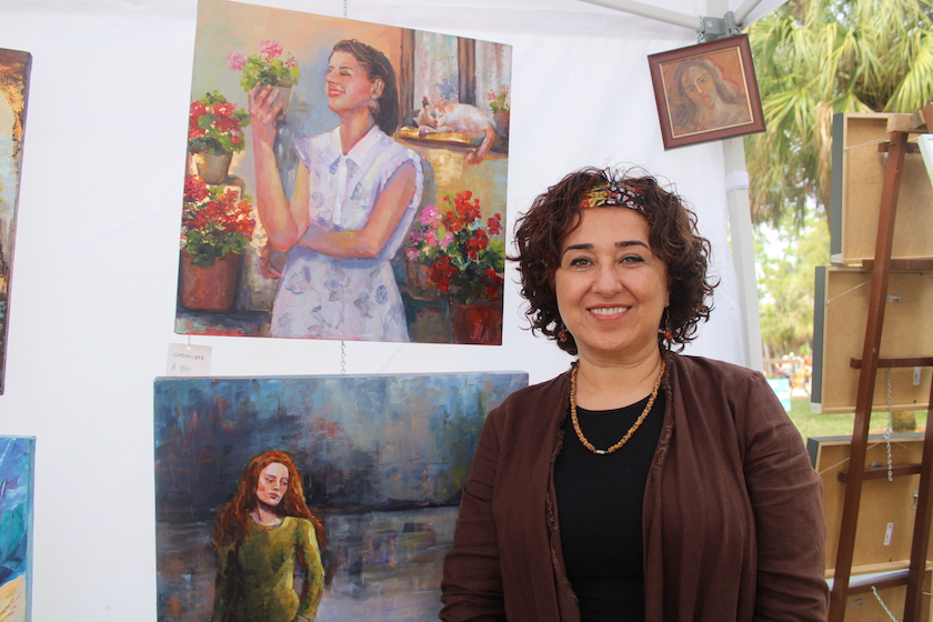 A woman standing next to two paintings of women on canvass