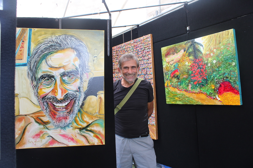 A man standing next to a self portrait painting and a colorful landscape painting.