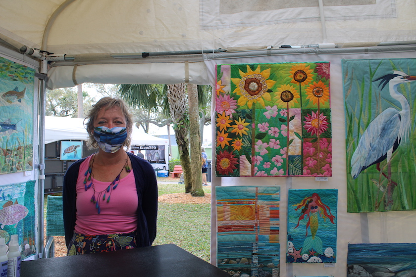A woman in a face mask next to colorful paintings of flowers.