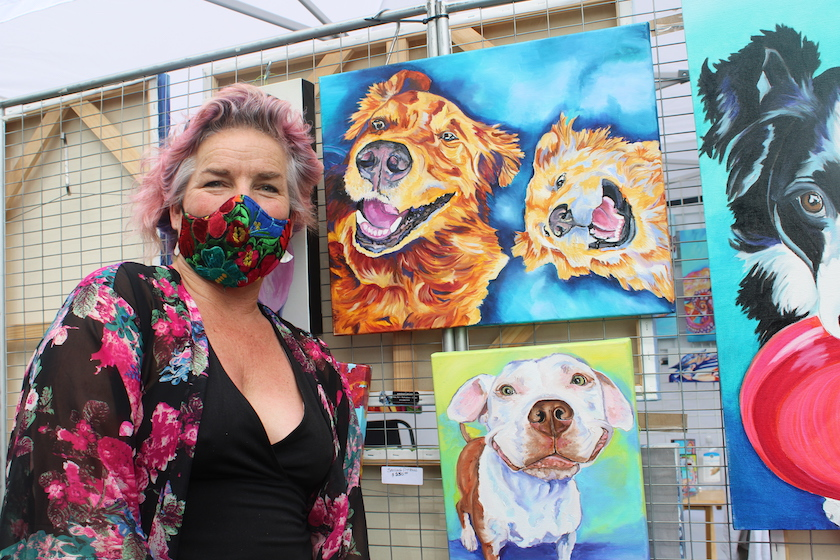 A woman in a face mask next to colorful paintings of dogs.