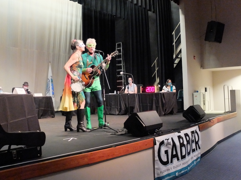 "A man and woman in costumes singing on a stage with a sign that reads ""Gabber"""