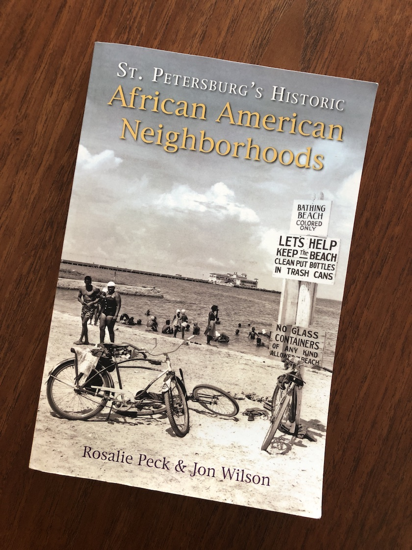 """The cover a book titled """"St. Petersburg's Historic African American Neighborhoods"""" with a vintage photo of a beach scene."""