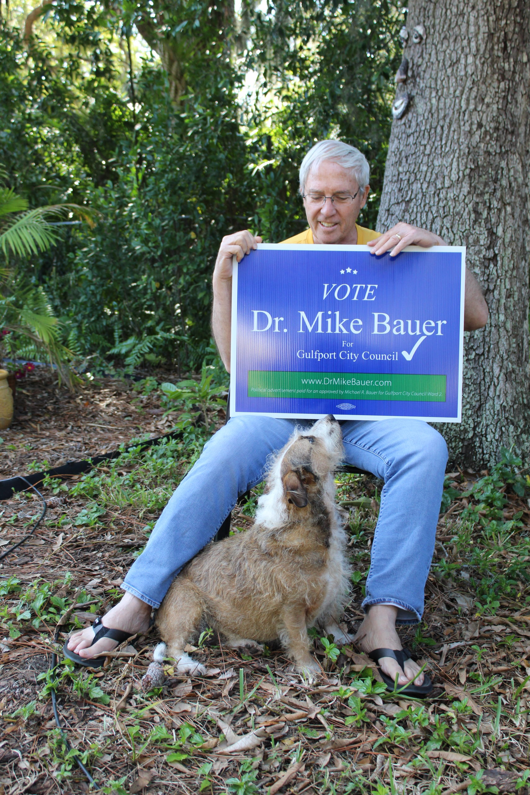 A man sitting in a yard with a dog, holding a sign that reads:Vote Mike Bauer""