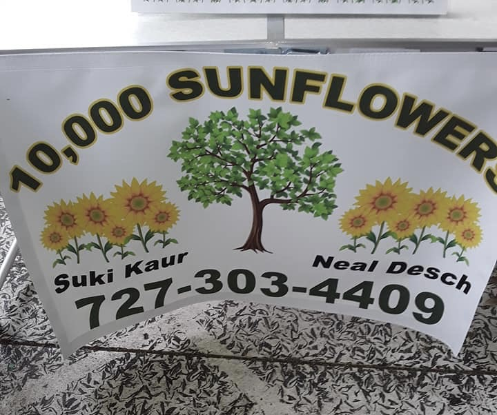 "A sign reading ""10,000 sunflowers with a phone number and a tree."