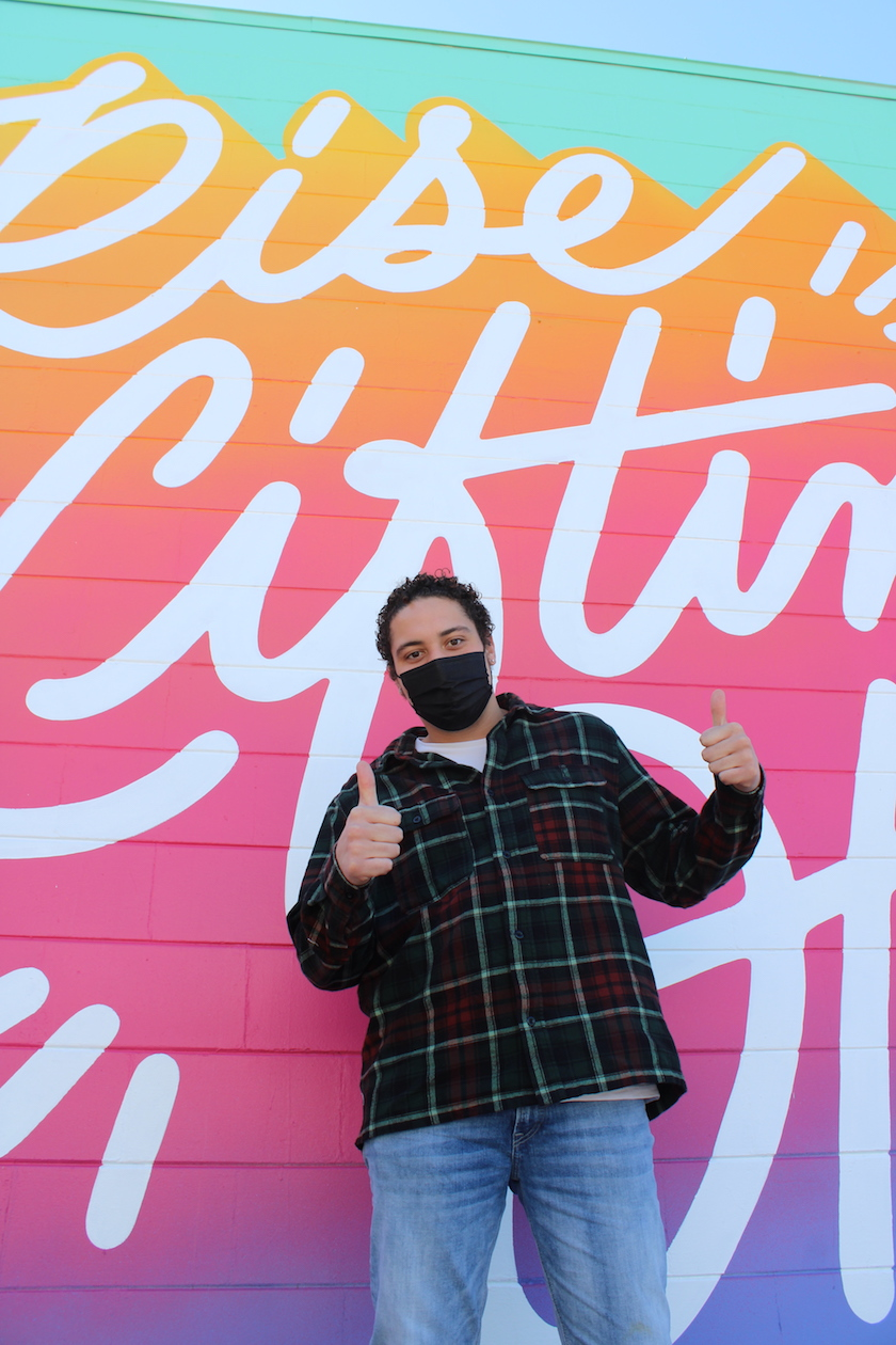 A person in a black face masks with thumbs up in front of a colorful mural