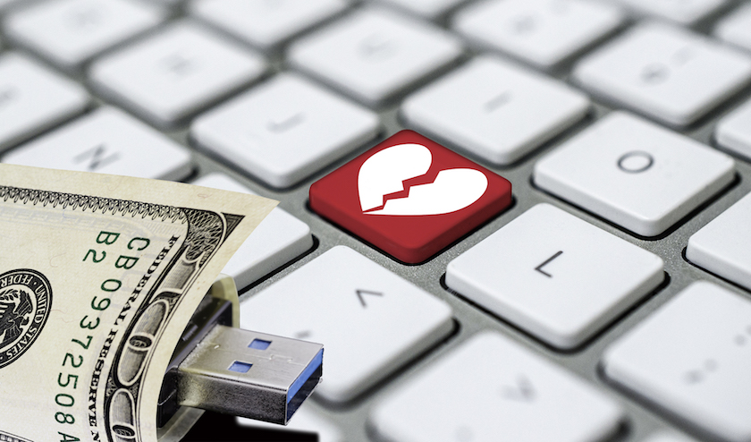 A keyboard with a broken heart key and a $100 bill