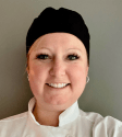 A headshot of a woman in a chef coat and hat