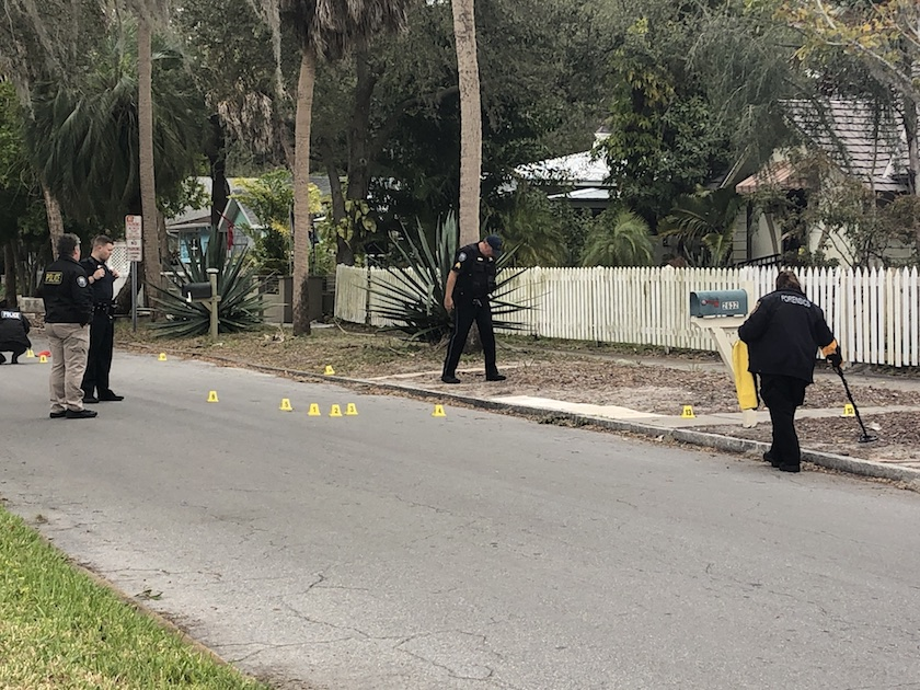 Police officers looking around a road with yellow evidence markers on the ground