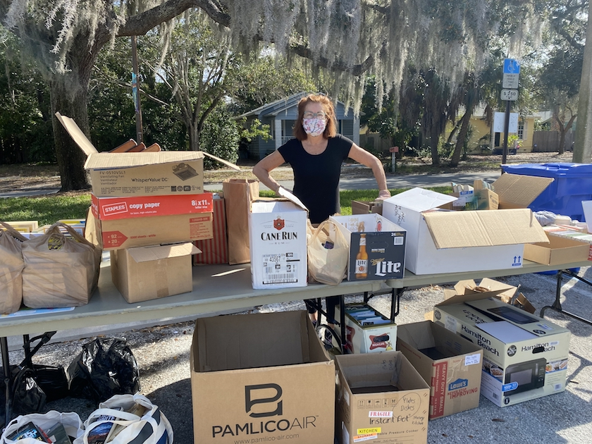 A woman in a face mask standing at an outdoor table full of boxes of books