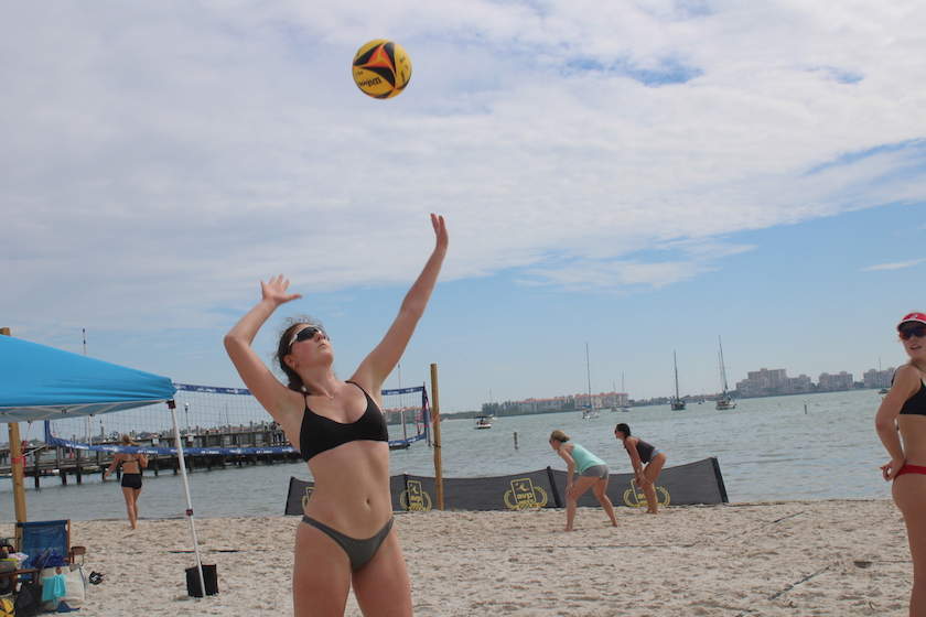 A woman playing volleyball on the beach