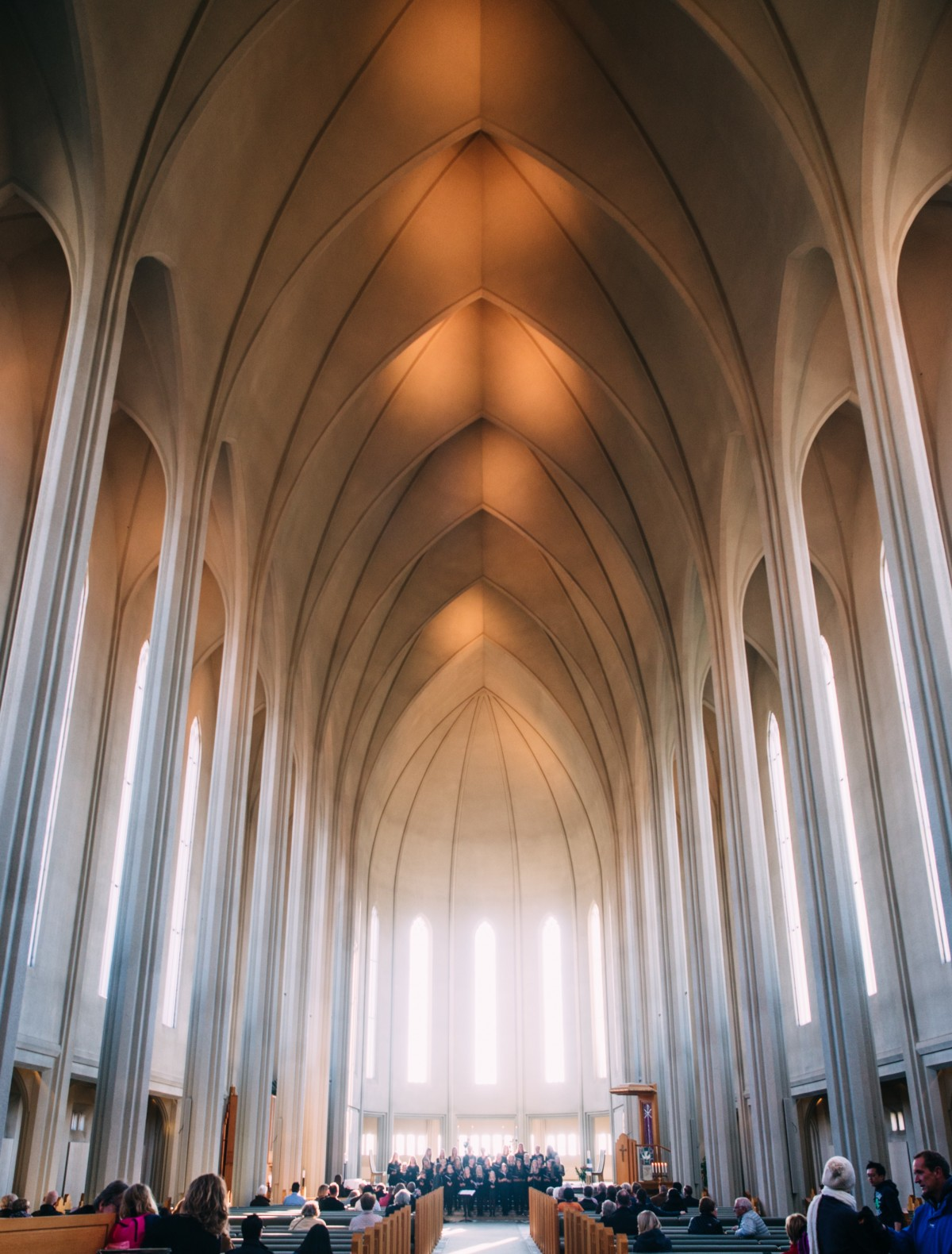 A sunlit cathedral with people in the pews