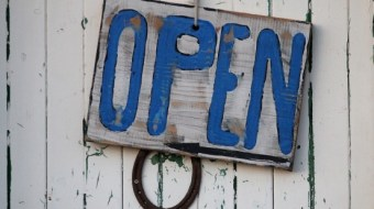 "Blue wooden sign that reads ""open"""