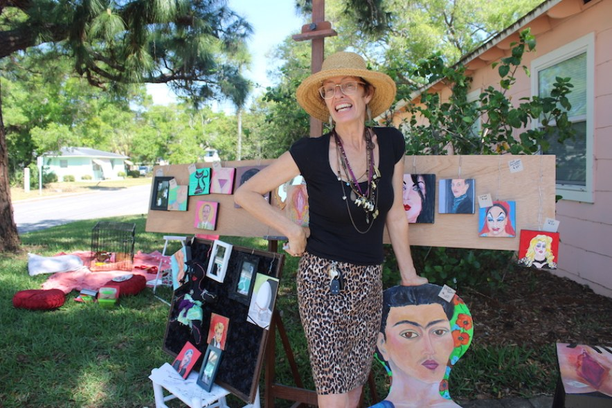 A woman in a hat and black top stands outside next to a display of art.