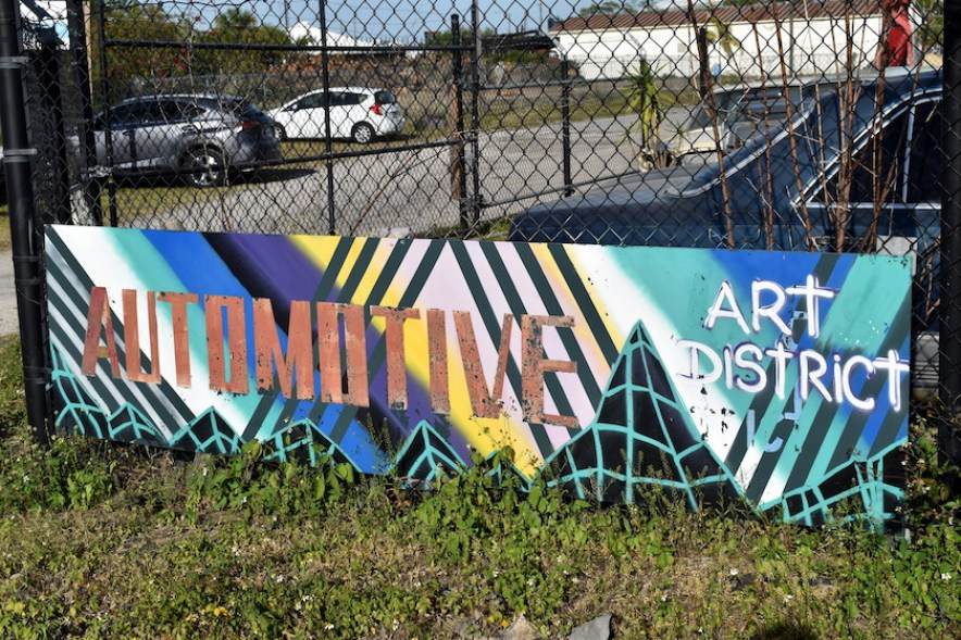 """A colorful sign against a chainlink fence that reads """"Automotive Arts District"""""""