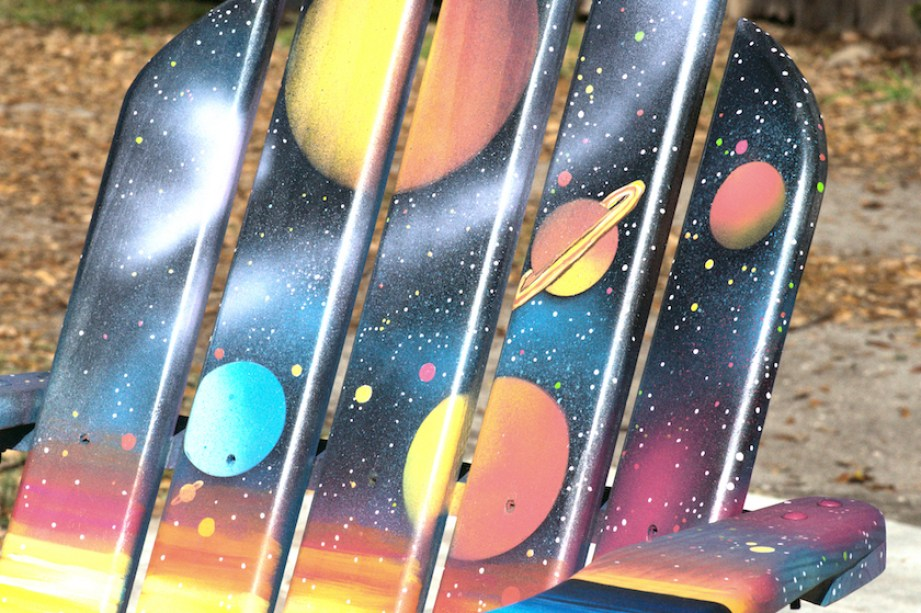 An Adirondack chair painted with planets and space objects