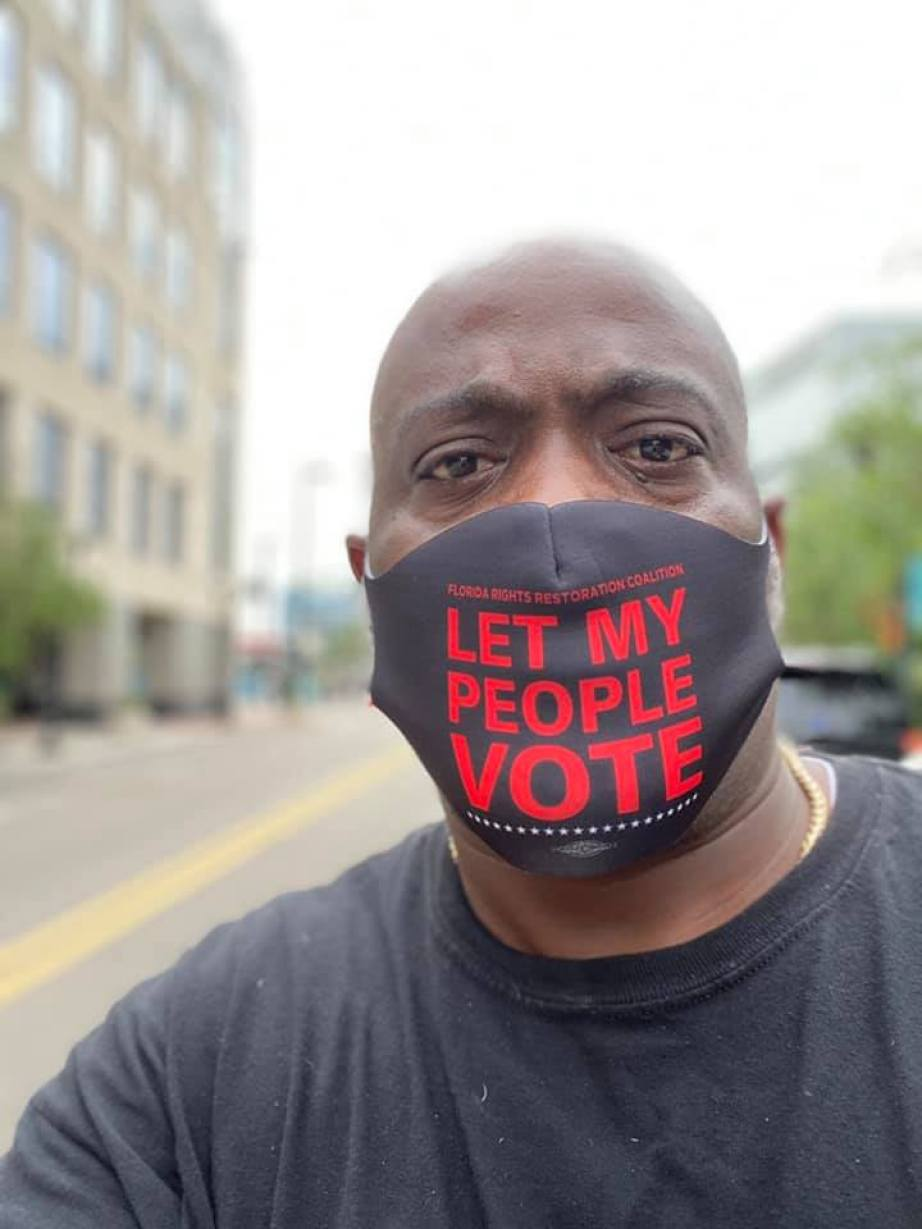 """A man in a face mask that reads """"Let My People Vote"""""""