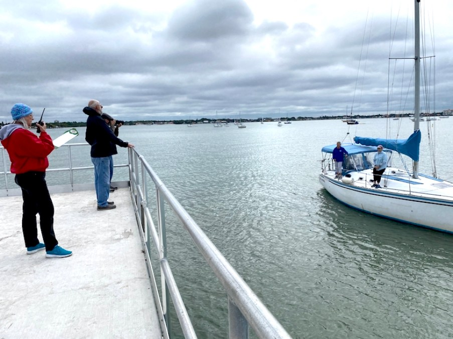A boat next to a pier with a man and woman standing on it in a overcast day