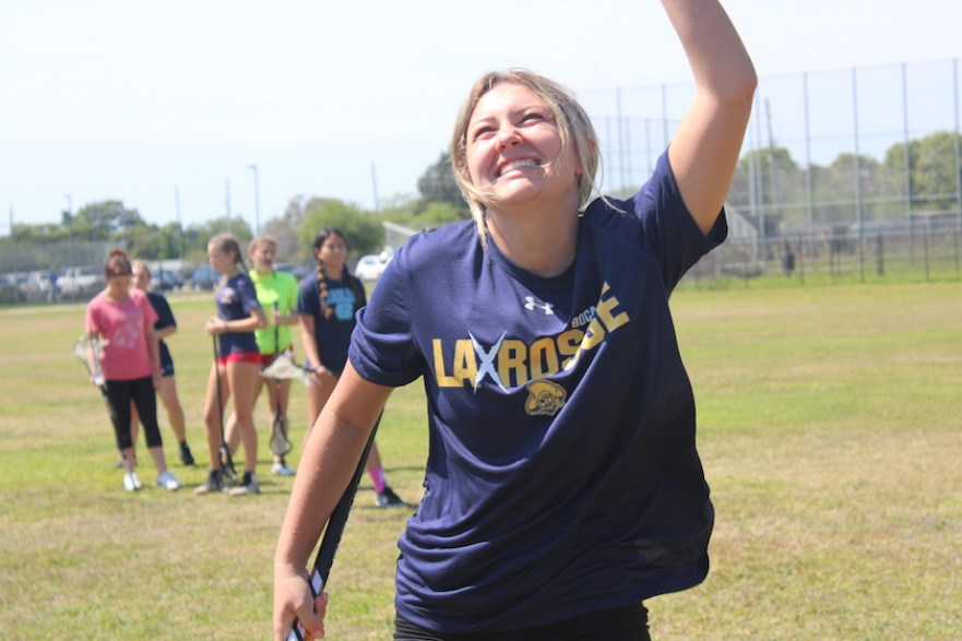 """A girl in a blue t-shirt that says """"Laxrosse"""" smiling with her hand in the air on a field."""