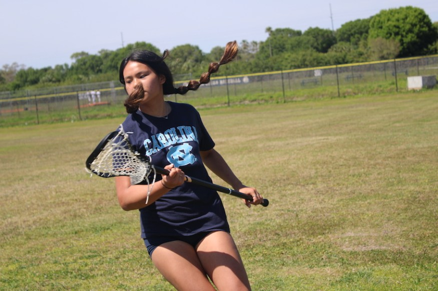 A girl in lacrosse uniform and stick on a field