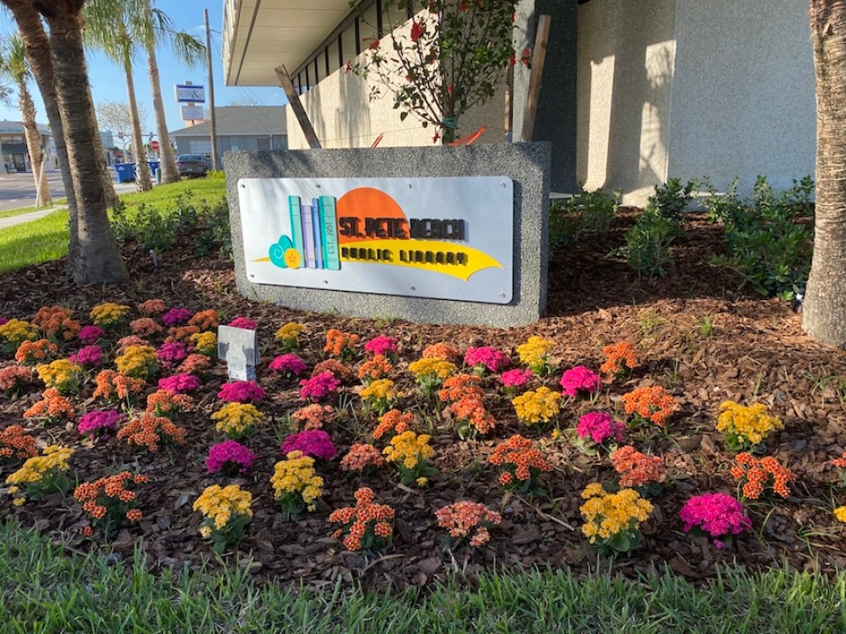 An outdoor sign for the St. Pete Beach Library in front of a landscaped area with yellow and pink flowers.