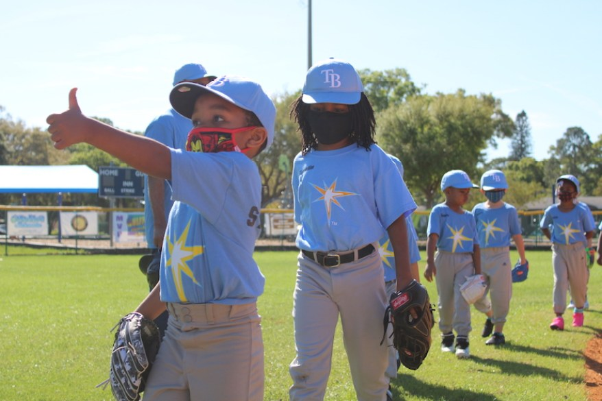 A group of kids in blue baseball uniforms