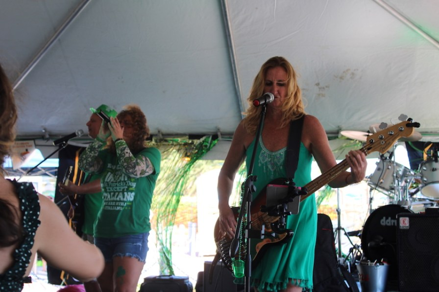 Women dressed in green on stage playing guitar and singing