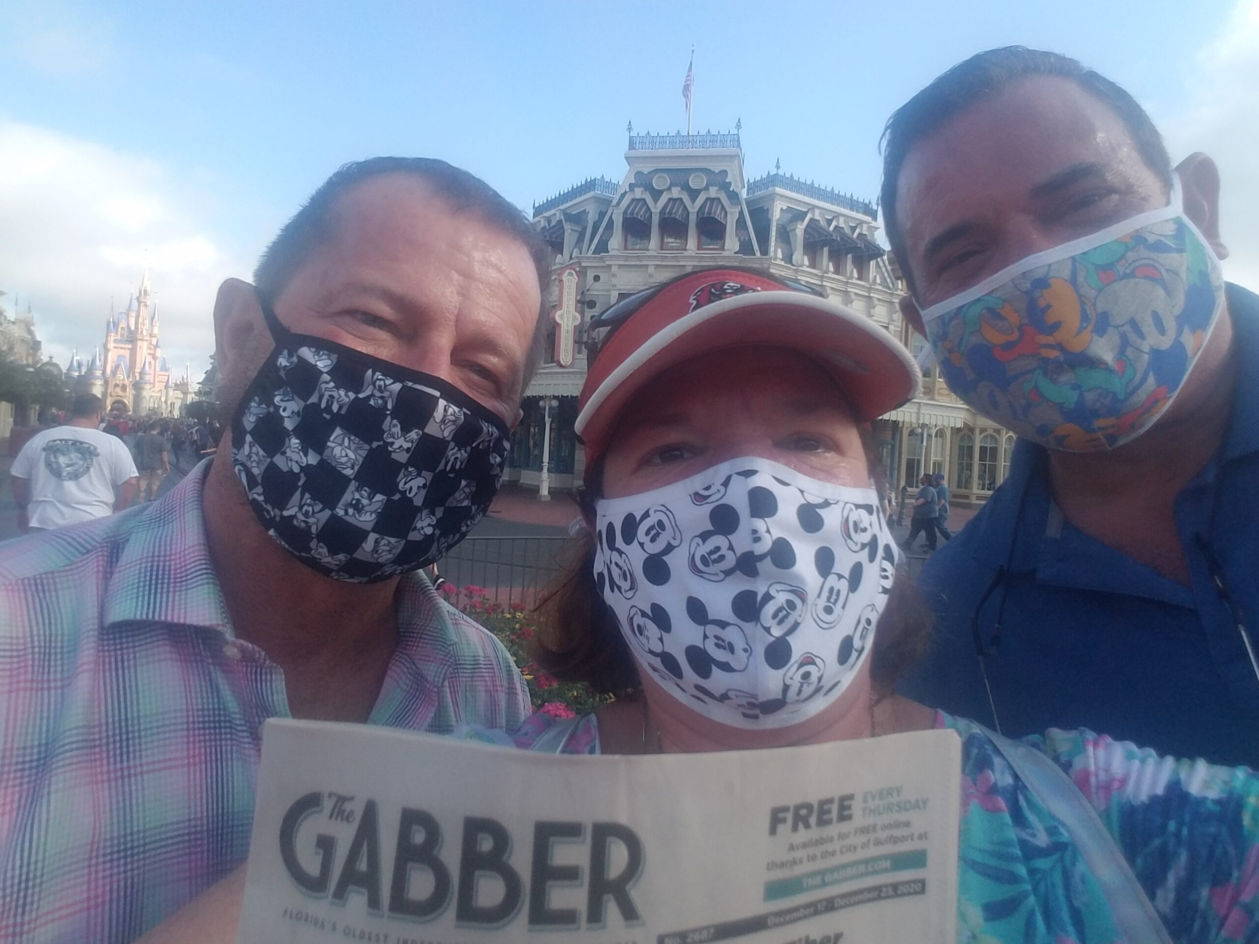 Three people in face masks holding a Gabber Newspaper