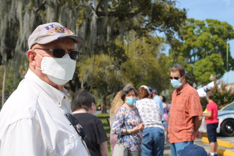 A man in a face mask and sunglasses outdoors in a crowd