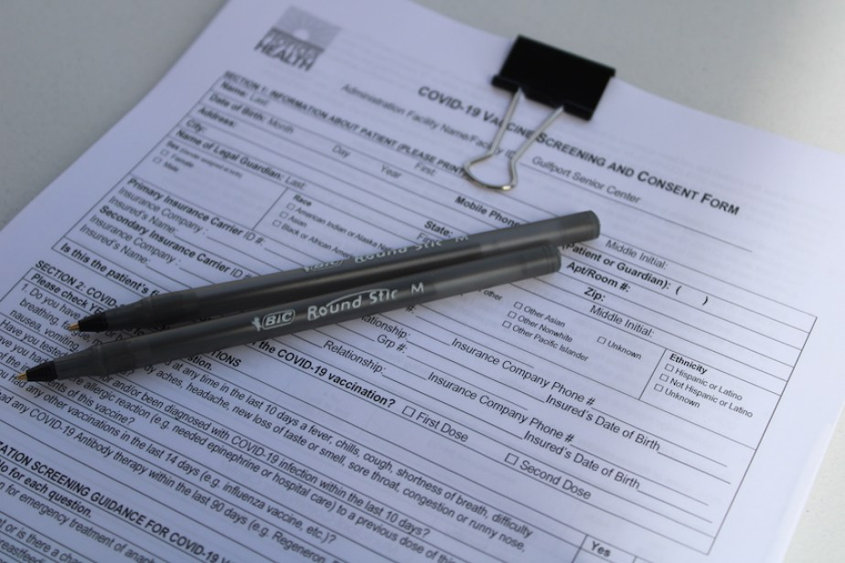 A consent for for COVID-19 vaccination on a clipboard with two black pens