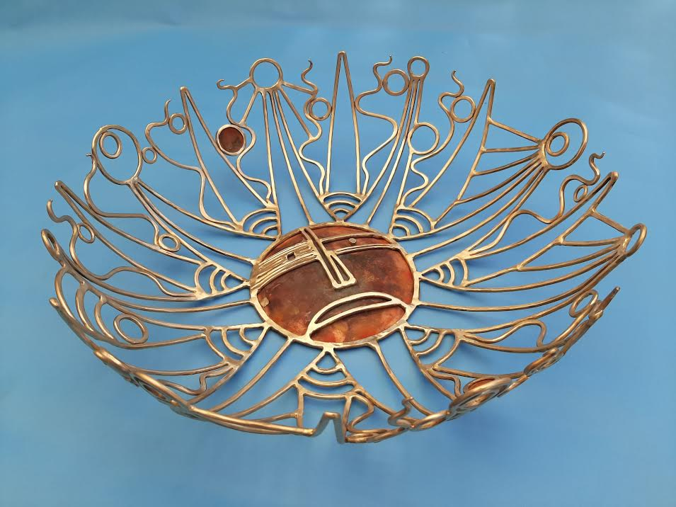 A gold glass decorative bowl on a blue background