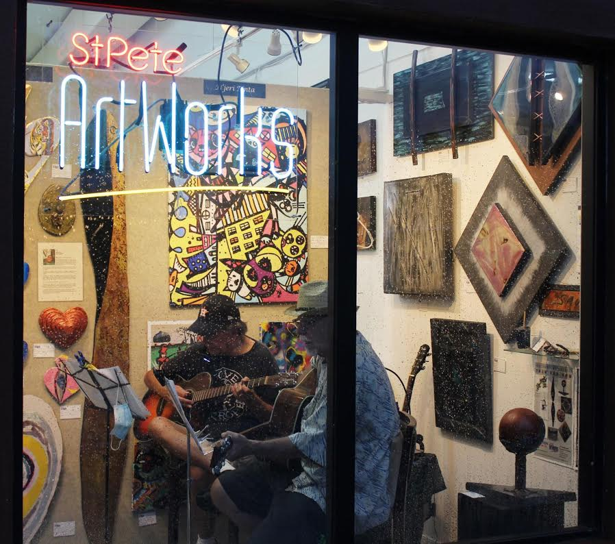 """A gallery space with a window and neon sign that reads """"ArtWorks"""""""