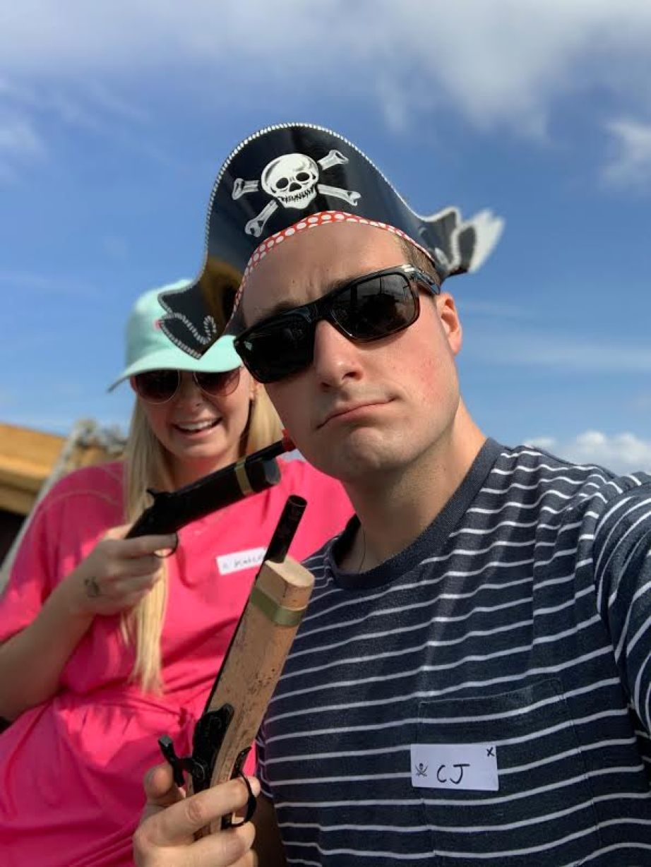 A man in sunglasses and pirate hat and stripped shirt taking a selfie with a woman in a pink shirt