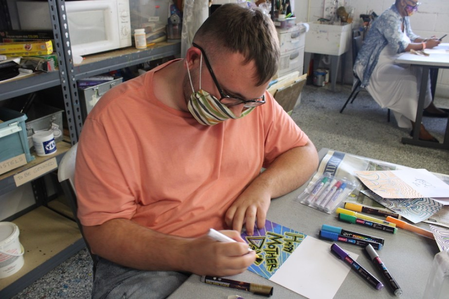 A young man sitting at a table wearing a face mask and peach t-shirt drawing a Mother's Day card.