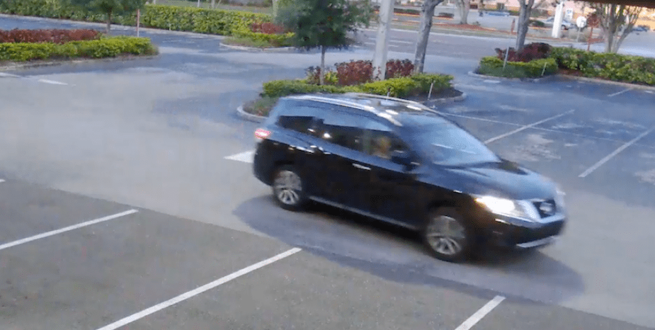 A photo taken from a video of a dark SUV driving in a parking lot.
