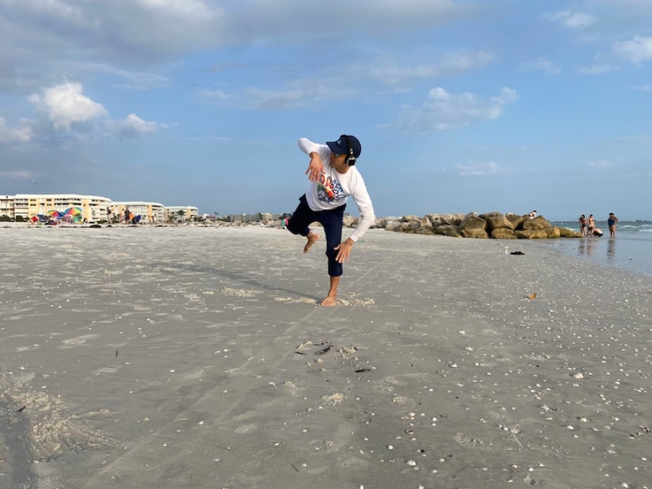A man dancing on a beach in the daytime.