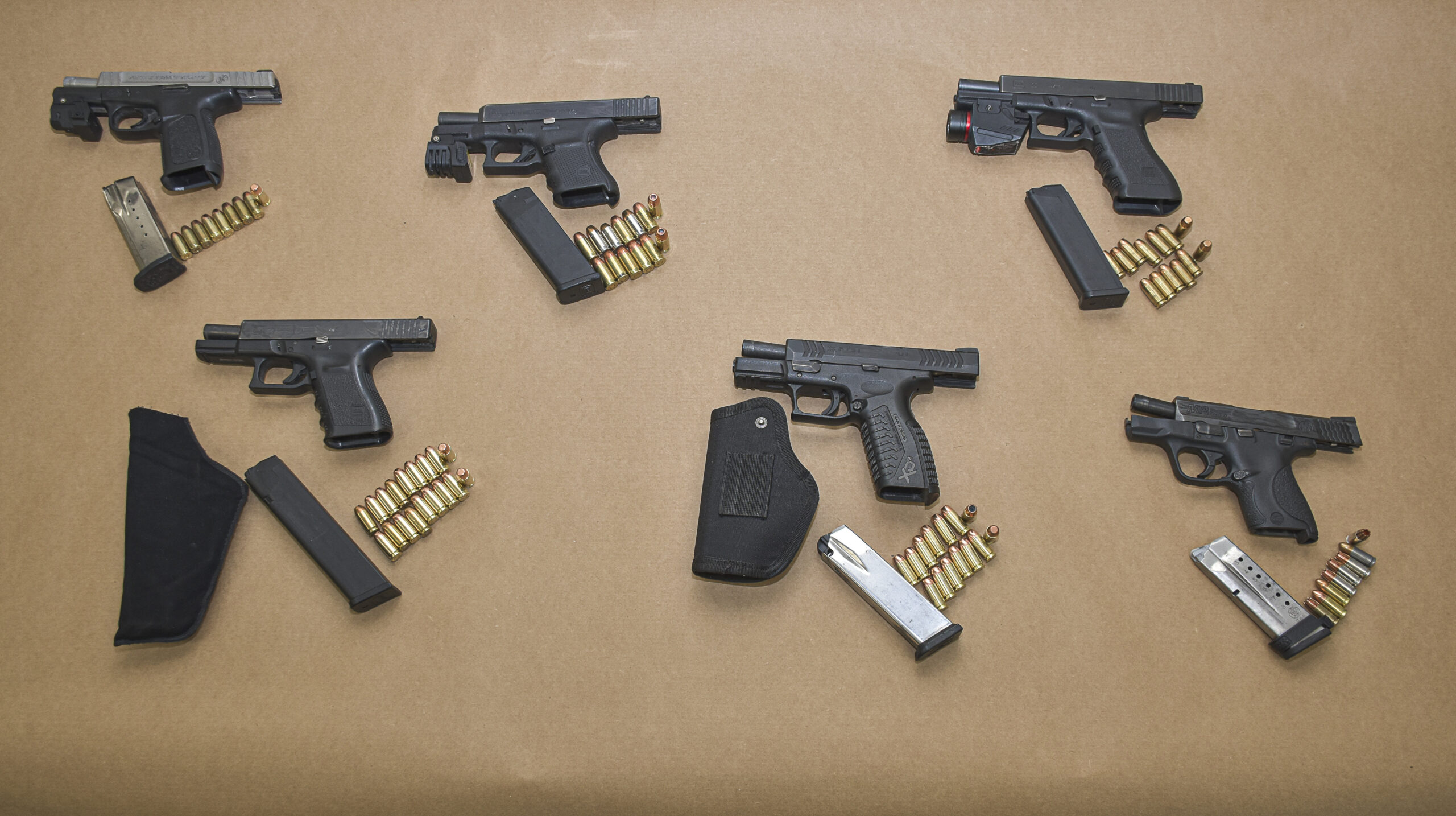 Multiple handguns and ammunition laid out of a brown surface.