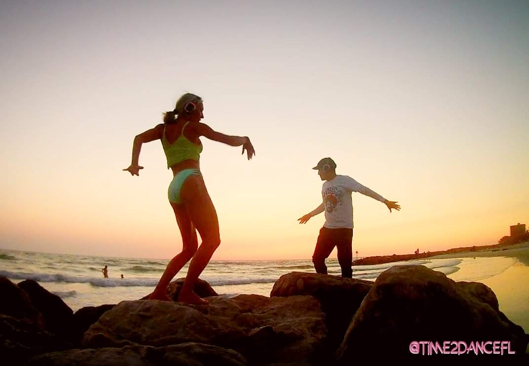 Two people dancing on a beach at sunset