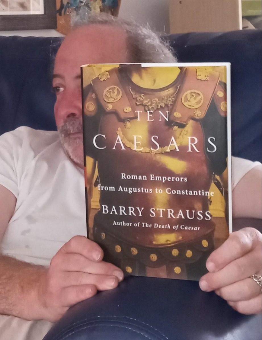 """A man holding up a book titles """"Ten Caesars"""""""