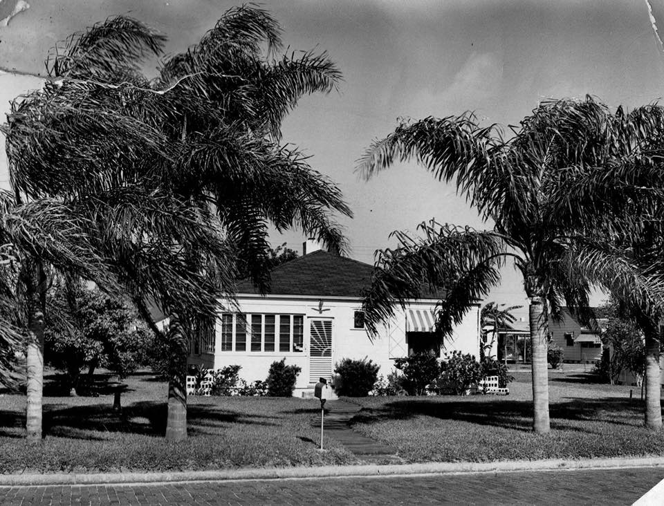 A black and white photo of a small white house surrounded by palm trees.