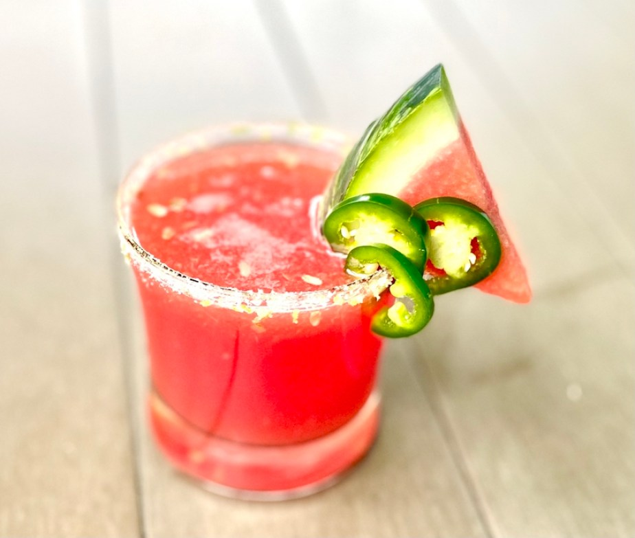 A picture of a pink cocktail with a slice of watermelon, jalepanos, and salt on the rim.