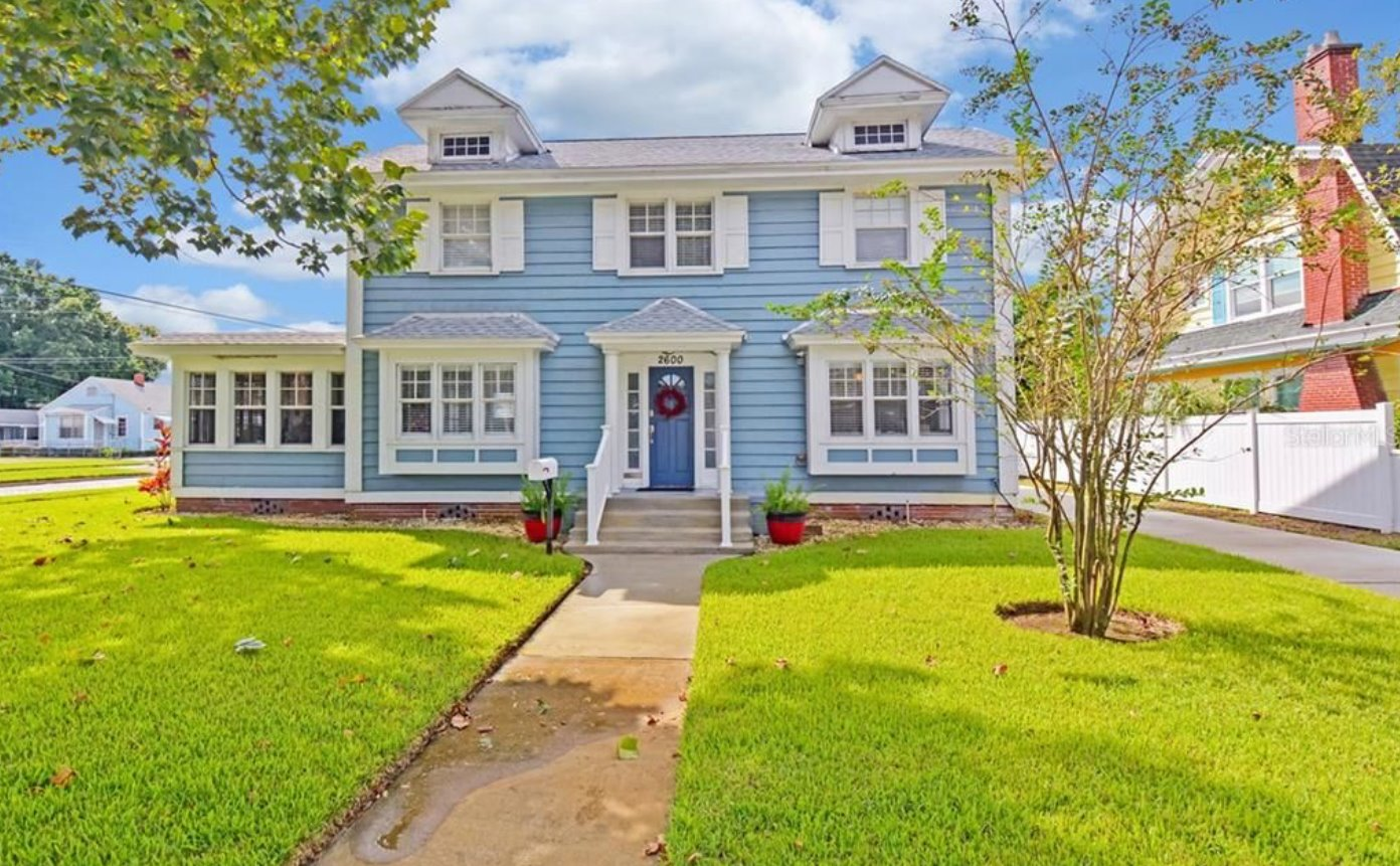 Photo of a blue colonial style two-story house with green lawn and trees.