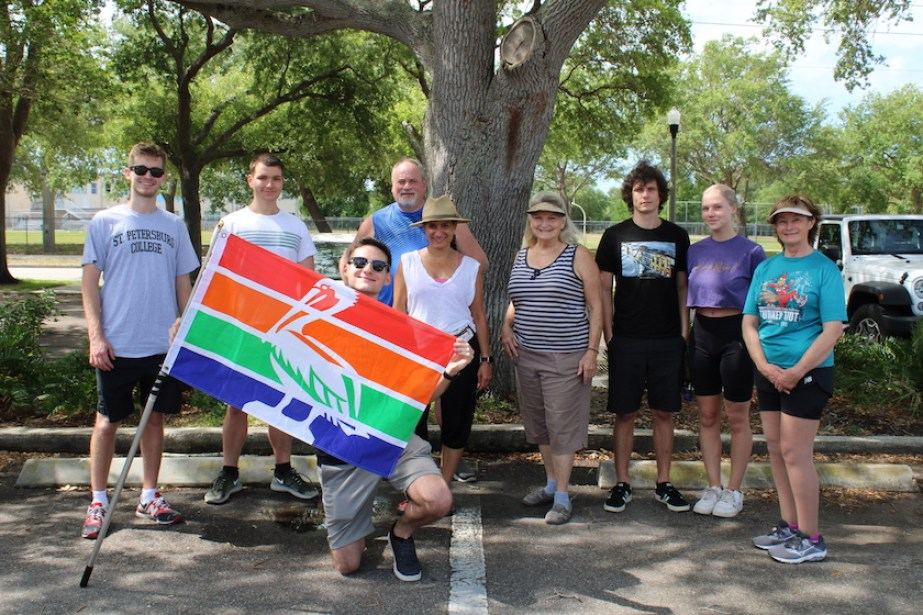A group of people posing for a photo with one holding a flag for the City of St. Petersburg, Florida