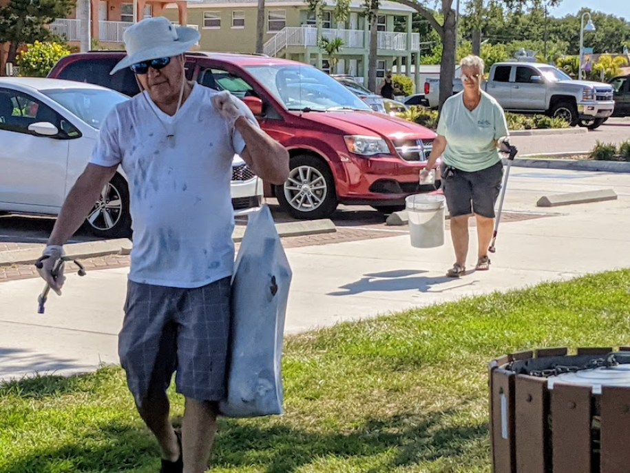 Two people in beach clothes carry cleanup supplies and a garbage bag outdoors