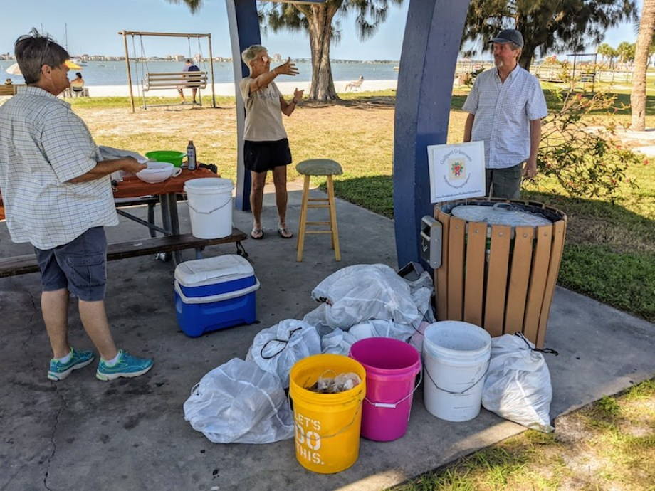 people gathered under a beach pavilion with cleanup supplies and bags of trash.