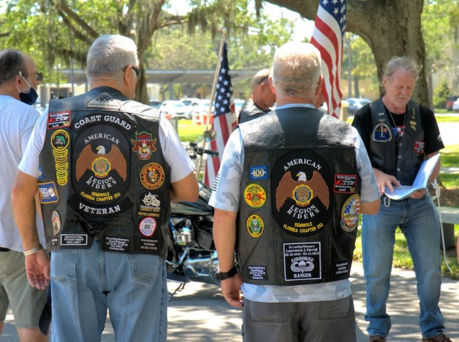 Two men in a group wearing vests with US military emblems on the back.