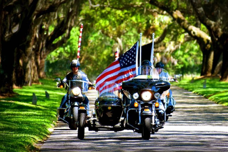 A group of motorcycles driving through a park with an American flag.